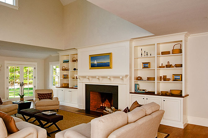 Custom built-in bookcases beside custom fireplace mantel.