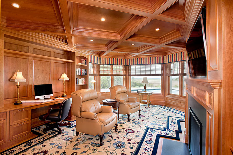 Custom office with built-in desk, wainscot, trim, and coffered ceiling.