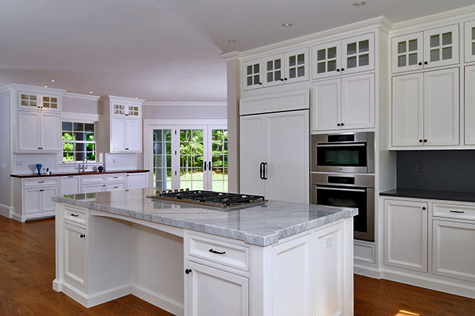 Cape Cod kitchen remodeled with white painted kitchen cabinets and island with seating.