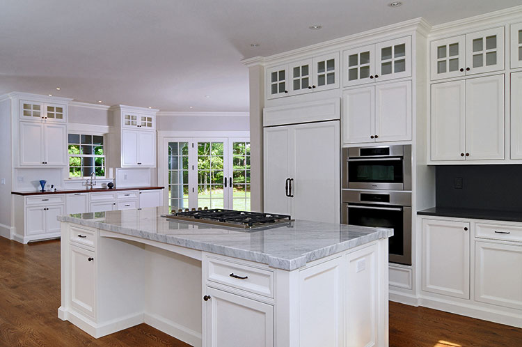 White painted kitchen cabinets with glass doors.