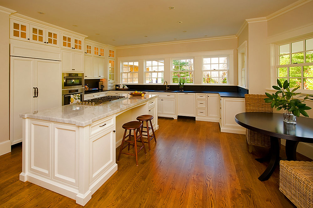 White traditional kitchen cabinets with custom island and stone countertops.